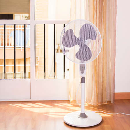 Electric fan that cools the air during a hot day at home.Photo