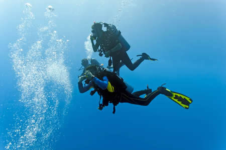 divers: Divers in the blue sea Stock Photo