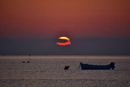 Red sunrise with silhouette of boat, South Italy Banque d'images
