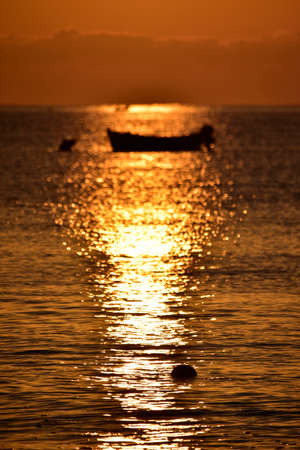 south italy: Red sunrise with silhouette of boat, South Italy Stock Photo