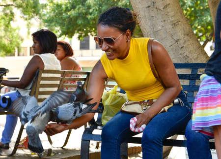 Santo Domingo, Dominican Republic. Woman feeds pigeons on Columbus Park, Colonial Zone of Santo Domingo. Editorial