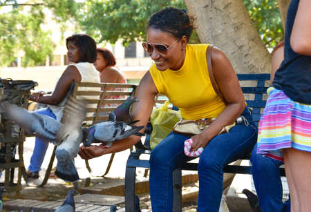 where to eat: Santo Domingo, Dominican Republic. Woman feeds pigeons on Columbus Park, Colonial Zone of Santo Domingo. Editorial