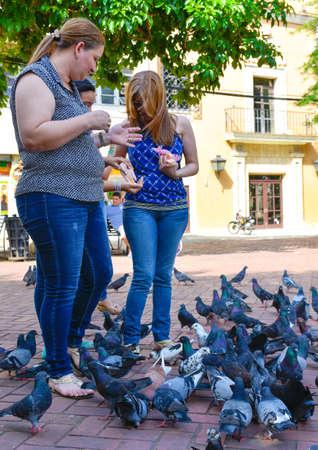 where to eat: Santo Domingo, Dominican Republic. Women feeds pigeons on Columbus Park, Colonial Zone of Santo Domingo.