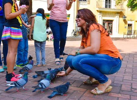 conde: Santo Domingo, Dominican Republic. Woman feeds pigeons on Columbus Park, Colonial Zone of Santo Domingo. Editorial