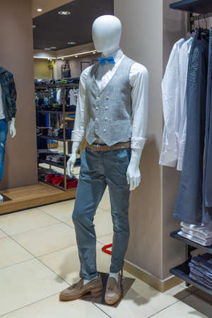 White mannequin in a store with gray vest and blue bow tie.