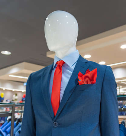 Close up of a mannequin in a blue jacket store, with a red tie and scarf.