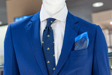 Close up of a mannequin in a blue jacket, with a blue tie and scarf.