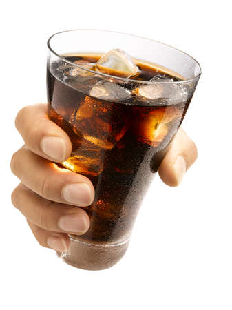 Hand holding a wet glass ice cold cola with ice cubes in it