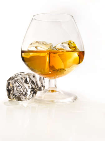 Glass of cognac with ice in a light environment