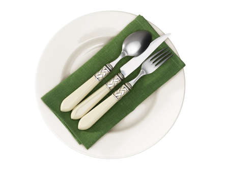 Cutlery laying on a green napkin on a ceramic plate.   Stock Photo