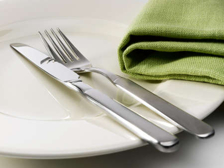 Silverware and a green napkin on a ceramic plate with