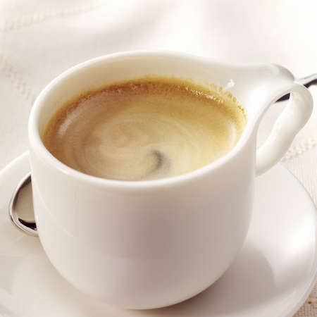 Espresso in a white cup with a nice curl in the foam on a white blank cloth.  Stock Photo