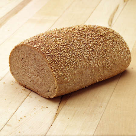 Sesame bread cut in half on a light wooden background.   Stock Photo