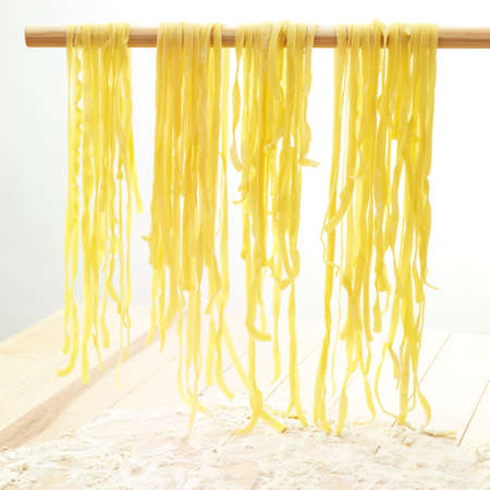 fresh tagliatelle shaped paste drying on a stick above wood and flower.