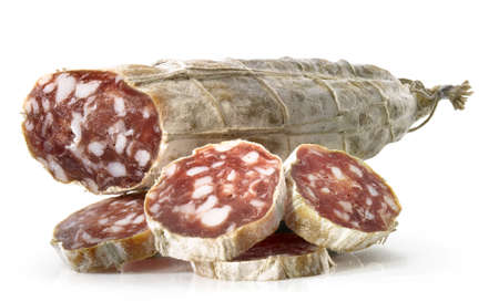 Close-up of a salami saucage with slices in front of it.