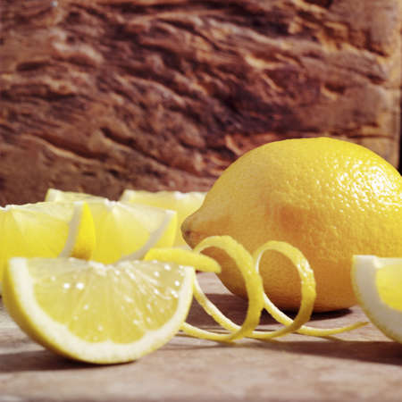Whole yellow lemon next to cut lemons with a zest in front of a stone background.   Stock Photo