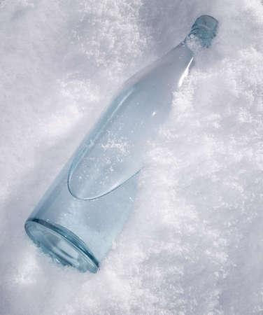 Bottle of wodka in the white crispy snow photo