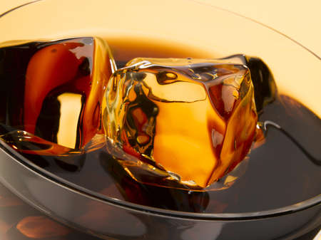 Close up of ice cubes floating in a glass of cola