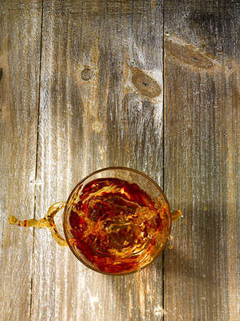 bourbon: Top shot with an icecube splashing in a glass of whiskey on a wooden background.