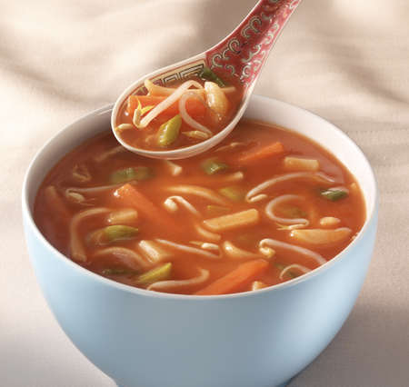 Bowl on a table with Chinese tomato soup and a traditional spoon hovering above