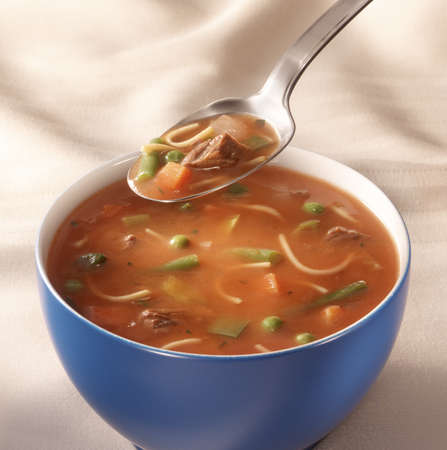 mushroom soup: bowl on a table with tomato vegetables soup and a spoon hovering above