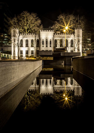 Mystic city hall of Tilburg at night with reflection in the water on Netherlands. Historic dutch architecture in down town. Tourist attraction. Night Photography
