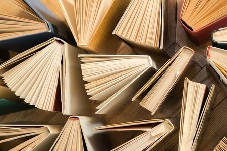 Libros de tapa dura viejos y usados, libros de texto vistos desde arriba sobre un piso de madera. Los libros y la lectura son esenciales para la superación personal, la adquisición de conocimientos y el éxito en nuestras carreras, negocios y vida personal. Foto de archivo