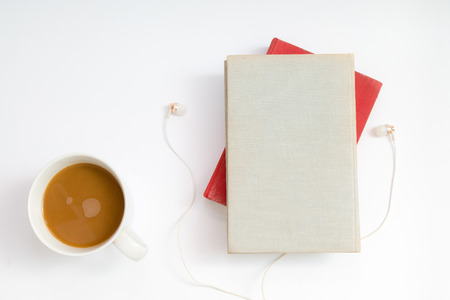 Audio book concept. Headphones, coffee and hard cover book over white table background. Top view with space for your text Stockfoto