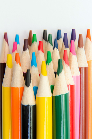 An assortment of colour pencils on white background. School supplies, creativity concept