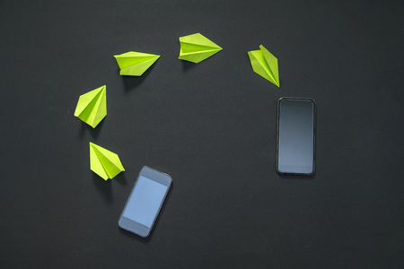 Share and send media files between phones. Paper planes, letter sent from phone to phone - technology linking people Stockfoto