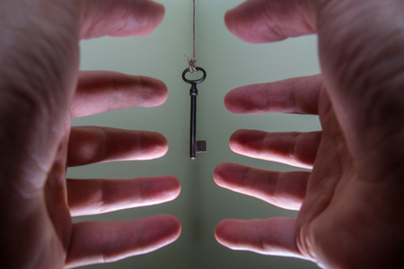 People hands reaching for vintage key hanging on a string. Business success freedom concept concept for aspirations, achievement and incentive