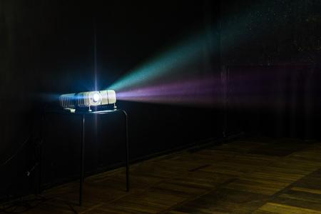 Nahaufnahme des Multimedia-Projektors mit bunten Lichtstrahlen, die auf die Leinwand projiziert werden Standard-Bild