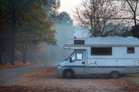 Old camper van parked in next to the road on foggy and cold autumn morning
