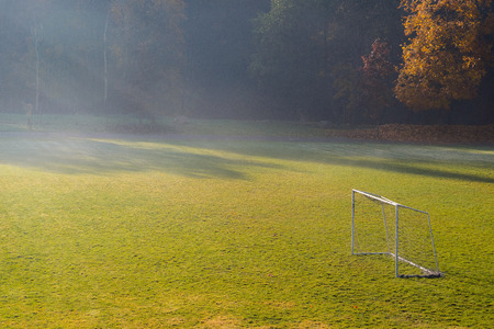 Early morning in the amatuer soccer field. Football game playground in autumn foggy morning. Early morning in the amatuer soccer field. Football game playground in autumn foggy morning. Sunlight in the background