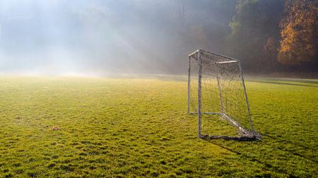 Am frühen Morgen auf dem Amateur-Fußballplatz. Fußballspielplatz im nebligen Herbstmorgen. Sonnenlicht im Hintergrund