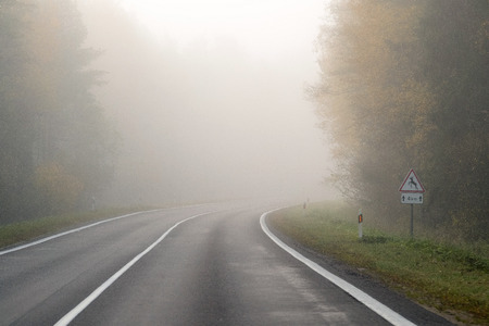 Driving on countryside road in fog. Illustration of dangers of driving in bad weather conditions: foggy, hard to see ahead