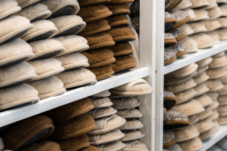 House slippers made of wool for the winter stacked on top each other in wooden cabinets