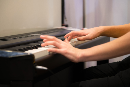Closeup humans hands playing electronic piano. Favorite classical music. Music classes, learning how to play musical instrument