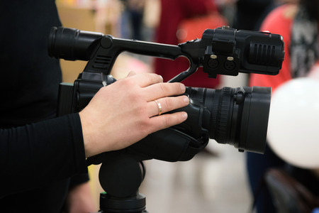 Covering an event with a video camera. Videographer films with video camera. Camera operator working indoors