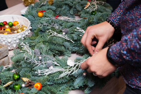 Christmas wreath weaving workshop. Woman hands decorating holiday wreath made of spruce branches, cones and various organic decorations on the table Imagens