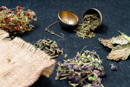 Different ding of teas on white background: green tea, red tea, thyme tea, cinnamon sticks, dried strawberries