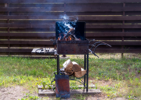 Burning firewood and preparing for barbecue outside in the harden. Concept of summer grilling, barbecue, bbq and party Stok Fotoğraf