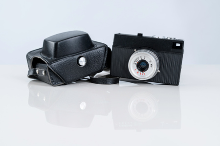 Old rangefinder film camera with a leather case on white background. Rustic vintage style