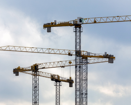 Industrial construction crane silhouettes isolated on blue cloudy sky