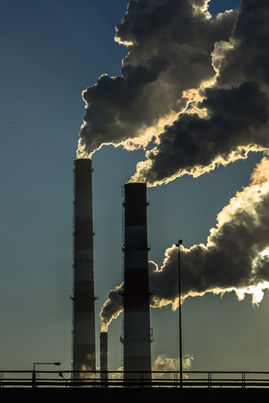 Dark Smoke from two industrial chimneys pipes on blue sky. Global warming. Air pollution. Standard-Bild - 117191897