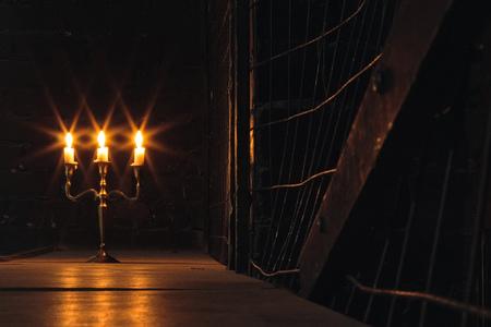 Groupe de bougies maléfiques brûlant dans l'obscurité et espace de copie sur fond en bois avec clôture métallique sur le côté. Rituel de magie noire ou rite d'halloween effrayant.