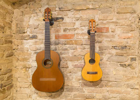 Two acoustic guitars hanging on brick wall background indoors. Vintage retro style