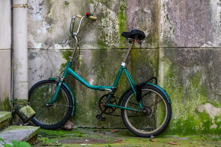 Vintage old green color school bicycle by the concrete wall