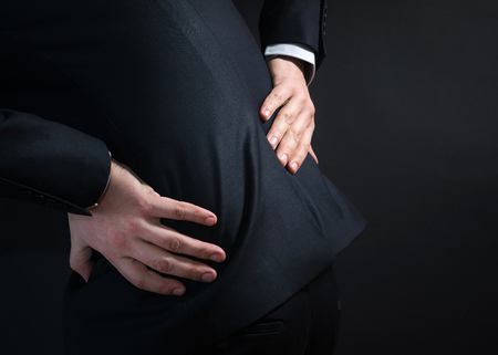 Businessman in a suit having a backache. Bending over in pain with hands holding lower back Stock Photo