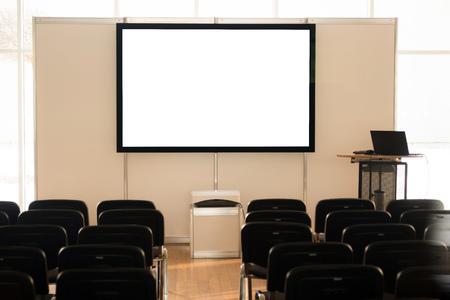 Pantalla vacía en sala de conferencias, sala de reuniones, sala de juntas, aula, oficina, con tablero de proyector blanco. Foto de archivo